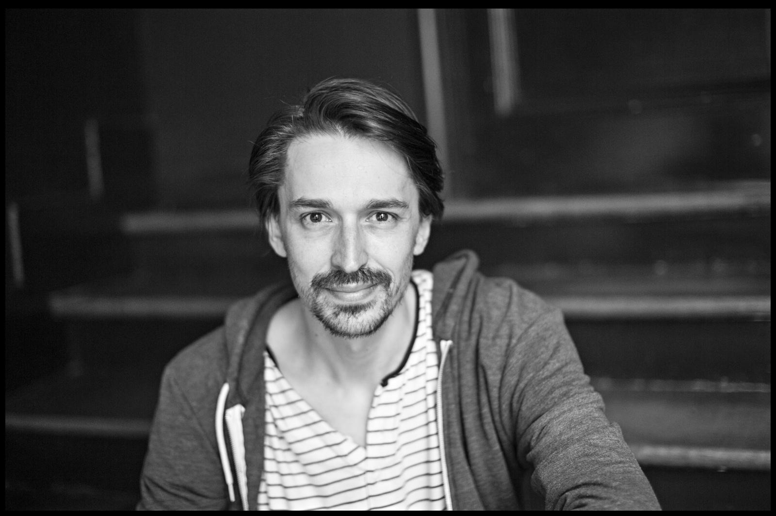 der Autor, ein schlanker, ca. 30-jähriger weißer Mann mnit leichtem Bart in Streifen-T-Shirt und Kapuzenpulli, auf Treppenstufen, blickt freundlich in die Kamera